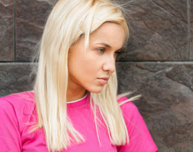 Blond girl in pink top with a withdrawn look on her face